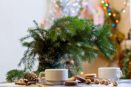 new year card: Coffee, tangerines, cookies and nuts in Christmas decor with Christmas tree, nuts and apples on colorful background bokeh Stock Photo