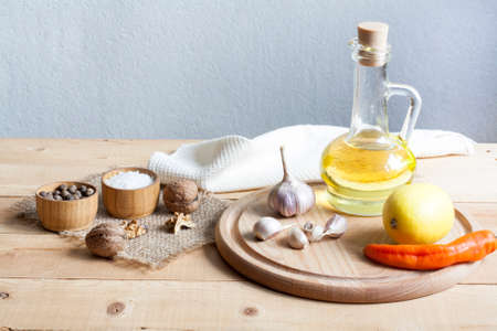 limon: Food ingredients. Oil, eggs, garlic, limon, walnuts and herbs on wooden table. Wooden board and napkin.