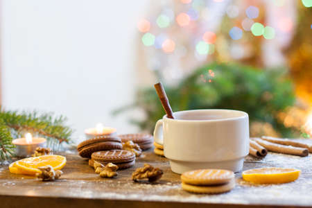 christmas tea: Tea with lemon, tangerines, cookies and nuts in Christmas decor with Christmas tree, nuts and apples on colorful background bokeh Stock Photo