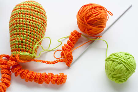 bibelot: Making of handmade colorful crochet toys sweets key ring with skein on wooden table. Selective focus.