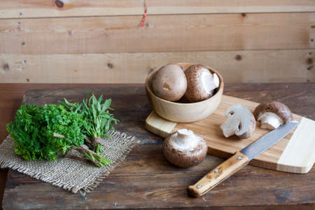 bagging: Champignon mushrooms, a knife, bagging and herbs on a wooden board on wooden background Stock Photo