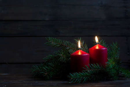 Christmas candles and lights. Two burning candles in with baubles and fir branch over wooden background, still life Stock Photo - 50709611