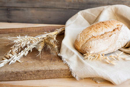 homemade style: Freshly baked homemade bread on a wooden table. Next to the bread wheat and oats ears. Rustic style. Closeup.