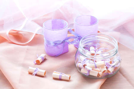rolled paper: Dreams written on a white rolled paper in a glass jar and two aromatic candles in glass candlesticks with lavender paper Stock Photo