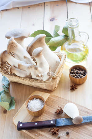 wooden basket: Basket with mushrooms, olive oil and ingredients for cooking on the wooden table of the kitchen background