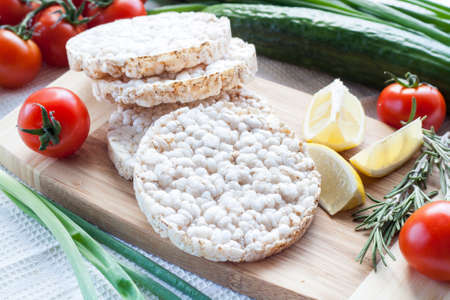Plain rice cakes, galette rice with lemon, rosemary and vegetables on wooden board Stock Photo