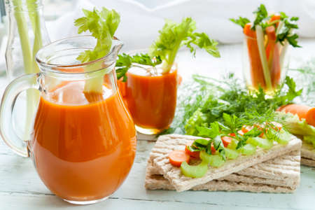 carrot cakes: Plain rye cakes, galette rye with fresh carrots, celery and parsley around fresh carrot juice, fresh carrot and celery on light background Stock Photo