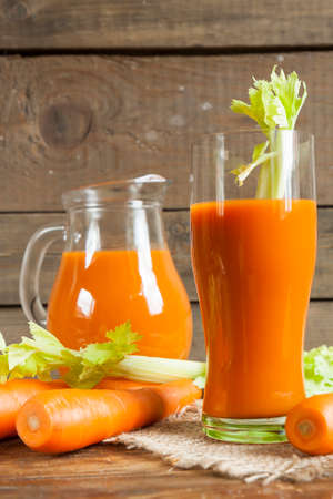carrot juice: Fresh carrot juice with carrots and celery on dark wooden background