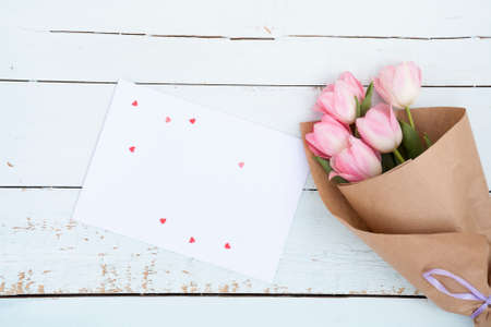 Beautiful bouquet of pink tulips next to a white envelope and pink sugar hearts on light wooden background Stock Photo