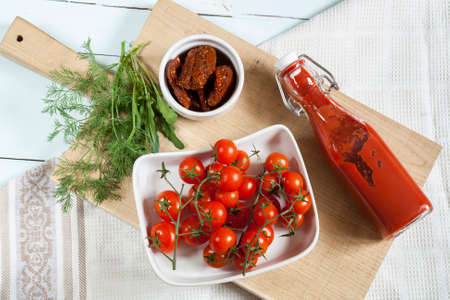 tomato puree: Sun-dried tomatoes, fresh tomatoes and tomato puree with arugula and dill on light wooden board Stock Photo