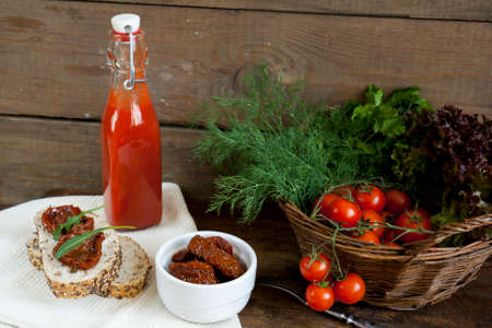 tomato puree: Sandwich with sun-dried tomatoes and arugula, sun-dried tomatoes, fresh tomatoes and tomato puree with parsley, lettuce and dill on dark wooden table
