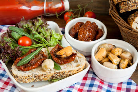 tomato puree: Sandwich with sun-dried tomatoes and arugula, sun-dried tomatoes, fresh tomatoes, bread, tomato puree and mussels with arugula and lettuce on light wooden board Stock Photo