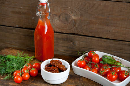 tomato puree: Sun-dried tomatoes, fresh tomatoes and tomato puree with arugula and dill on dark wooden table