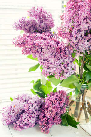 syringa: Branches of flowering purple lilac syringa in a glass jar on light table. Coloring and processing photos in vintage style with soft selective focus. Beautiful spring floral background. Stock Photo