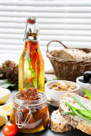ceramic bottle: Dried tomatoes in jar and bottle of olive oil with spices, mussels and black olives and in ceramic bowls, bread, fresh tomatoes, sliced lemon, herbs on black stone board. Mediterranean food on black stone board