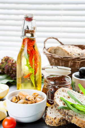 ceramic bottle: Bottle of olive oil with spices and mussels and black olives and in ceramic bowls, bread, dried tomatoes in jar, fresh tomatoes sliced lemon, herbs on black stone board. Mediterranean food on black stone board Stock Photo