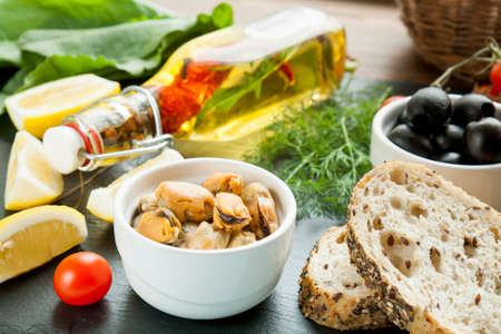 ceramic bottle: Mussels and black olives and in ceramic bowls, fresh tomatoes, sliced lemon, bread and bottle of olive oil with spices on black stone board. Mediterranean food on black stone board