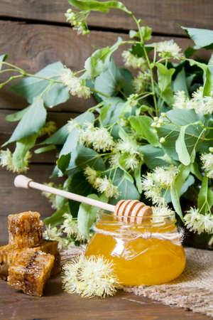 linden flowers: Jar with honey, honeycomb with pollen and linden flowers on a dark wooden background Stock Photo