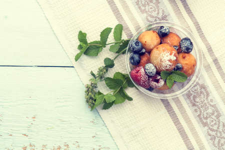 field mint: Breakfast, with cottage cheese balls with raspberry, blackberry and blueberry and mint on light table.  Toned and processing photos with soft selective focus. Shallow depth of field