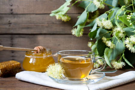 Linden tea in glass cup and jar with honey with linden flowers on a dark wooden background Stock Photo
