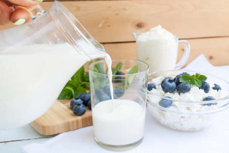 bilberry: Pouring milk in the glass on the table with other dairy products, bilberry and fresh mint Stock Photo