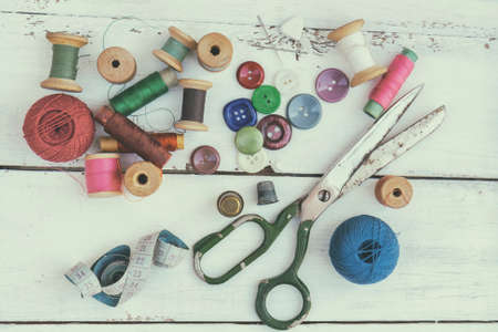 Set of several pied buttons for garment with threads, garment tape and scissors on a bright wooden background. Toned and processing photos with soft focus in vintage style.