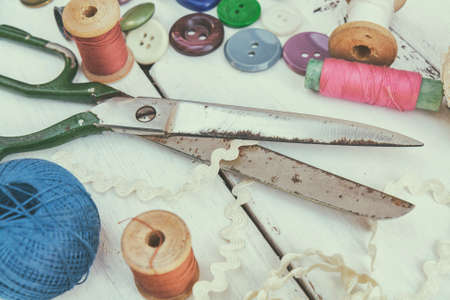 bead embroidery: Set of several pied buttons for garment with threads, garment tape and scissors on a bright wooden background. Toned and processing photos with soft focus in vintage style.