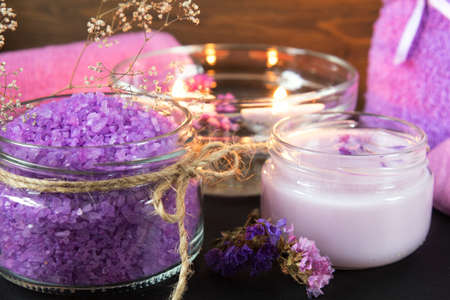 Spa products. Lavender bath salts, dry flowers, cosmetic cream, light candles and towel. Violet purple concept. Coloring and processing photo.