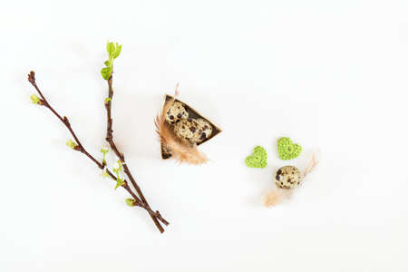 Easter holiday attributes sets. Quail eggs, green woolen crochet hearts, feathers, cherry and apricot branches on white background. Easter holiday eco concept. Stock Photo