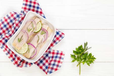 Snijd haringfilets, snijd de ui en limoen op een witte plaat. Geruit servet. Op houten tafel. Stockfoto