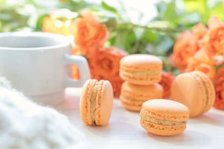 Orange mango or citrous macaroons, cup of coffee and fresh little roses on light wooden background. Sunlight. Coloring and processing photo with light vintage style. Shallow depth of field.