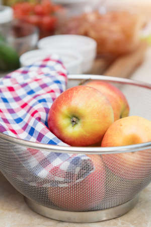Raw fresh red apple with checkered napkin in sieve in a modern kitchen. Shallow depth of field. Toned. Stock Photo