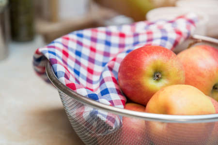 stuffing: Raw fresh red apple with checkered napkin in sieve in a modern kitchen. Shallow depth of field. Toned. Stock Photo