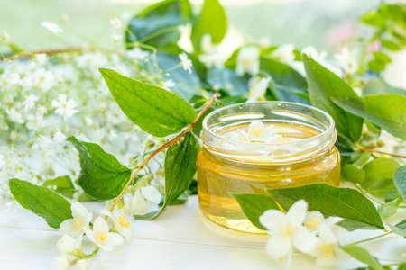 Honey in glass jars with jasmine flowers on windowsill. Shallow depth of field.