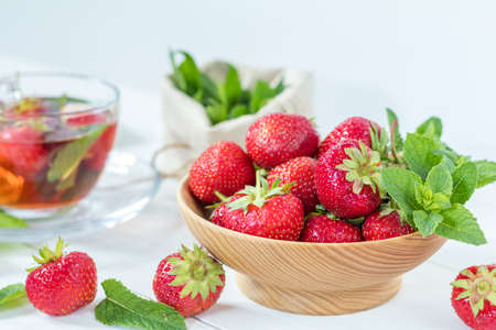 shallow: Fresh strawberry in wooden plate. Glass cup of summer tea with fresh strawberry. Green leaves. Fresh mint. White wooden table. Shallow depth of field.