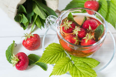 Glass cup of summer tea with fresh strawberry. Green leaves. Fresh mint. White wooden table. Shallow depth of field. Stock Photo