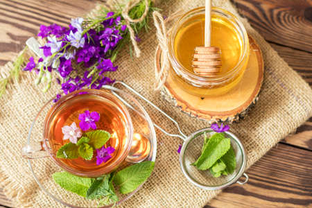 Glass cup of summer herbal tea with fresh mint and field larkspur. Jar of honey. Wooden table. Shallow depth of field.