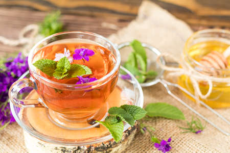 herbalism: Glass cup of summer herbal tea with fresh mint and field larkspur. Jar of honey. Wooden table. Shallow depth of field.