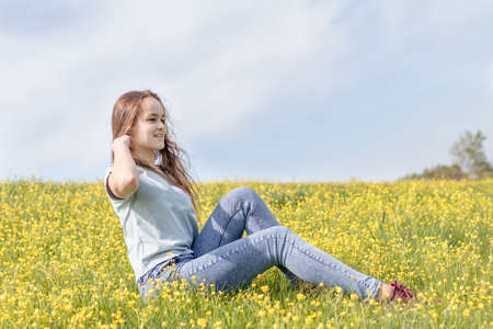 yellow teeth: Young girl teenager on a lawn field with yellow flowers. Long chestnut hair. Sunshine, springtime, blue sky. Coloring and processing photos with soft selective focus. Shallow depth of field. Stock Photo