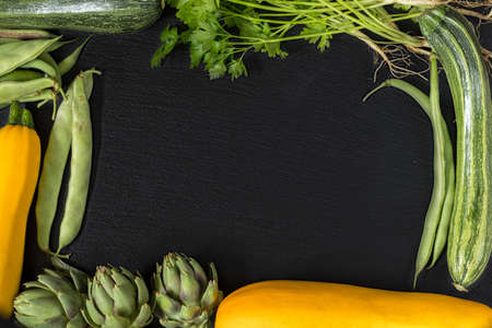 Fresh organic green vegetables on black stone floor with copy space. Green and yellow vegetables background. Healthy eating background. Vegetarian food, organic food.
