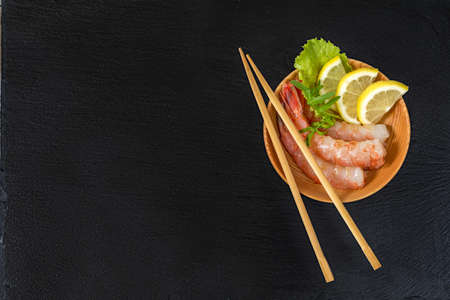 Cooked peeled shrimps with lemon slices, green lettuce and arugula leaves on a wooden plate with wooden chopsticks on a side of a plate. The plate is at the black stone countertop Stock Photo