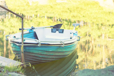 Sunny spring day in the city park with a pond surrounded by rocks. Trees reflection in the water. Blue wooden boat with two paddles peacefully resting in the pond. Stock Photo