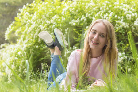 Cute blonde teenage-girl dreaming on a sunny day on the grass in front of the blooming bushes in the springtime