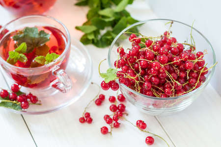 Fresh juicy redcurrant in clear glass vase. Shallow depth of field Stock Photo