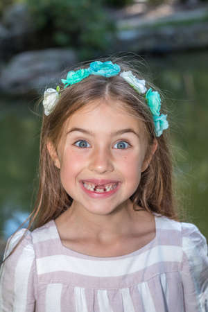 Funny portret of little girl who lost front teeth. City park in the summer time