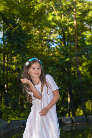 vestidos de epoca: Cute little girl making funnie faces in the city park in the summer time Foto de archivo