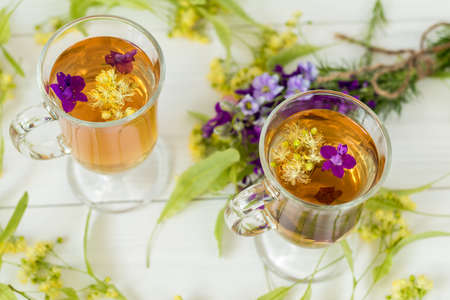Linden herbal tea in a transparent grog glass with a linden blossom and bunch of herbs on the white wooden surface Stock Photo