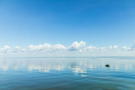 Amazing beautiful blue sky with light white clouds over calm smooth river surface. Summertime. Sunny day. Stock Photo
