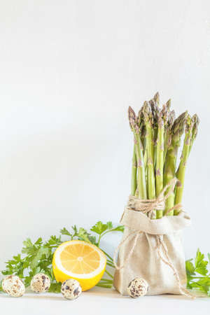 Bunches of fresh asparagus in a little sack, lemon and quail eggs on the white cracked wall background. Copy space Stock Photo