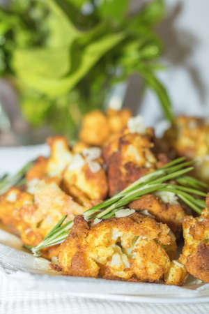 Fried cauliflower in batter on a white plate with white napkin. Close-up Foto de archivo